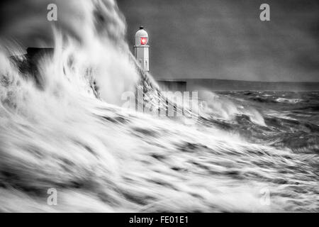 Black and white of large waves colliding into the sea wall as storm hits  Lighthouse, Porthcawl.  Bridgend, South - Stock Photo