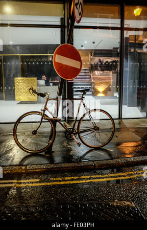 A bicycle chained to a no entry sign in central London, seen at night. - Stock Photo