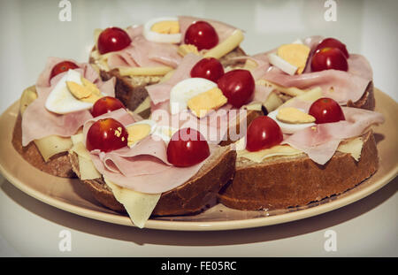 Tasty sandwiches with egg, cheese, ham and cherry tomatoes on the plate. Food theme. - Stock Photo