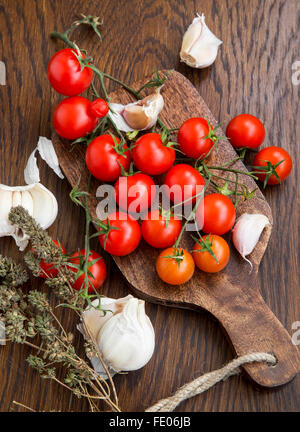 Organic cherry tomatoes with garlic and thyme herb on a wooden table - Stock Photo