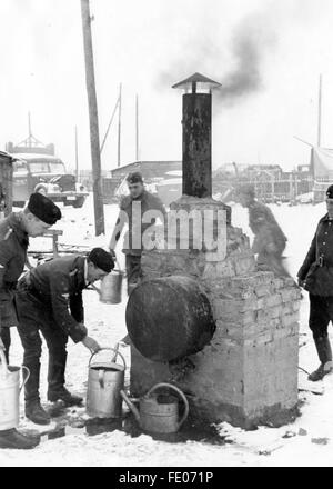 The Nazi propaganda picture shows workers of the Todt Organisation standing around an oven to warm up water and - Stock Photo