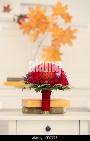 autumn bridal bouquet of red color with books on a dresser - Stock Photo
