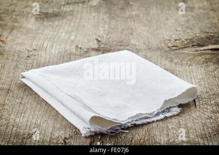 White cotton napkin on old wooden table - Stock Photo
