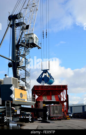 A 'Clamshell bucket' on the wire rope of a dock-side crane - Stock Photo