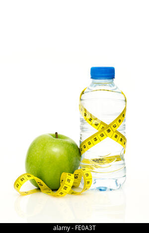 Water bottle wrapped in yellow tape measure with green apple isolated on white background with copy space - Stock Photo