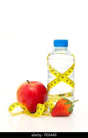 Water bottle wrapped in yellow metric tape measure with red apple and strawberry isolated on white background with - Stock Photo