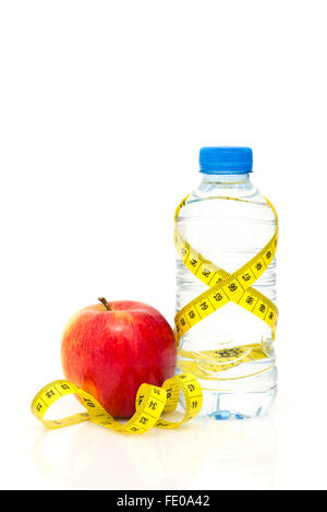 Water bottle wrapped in yellow metric tape measure with red apple isolated on white background with copy space - Stock Photo