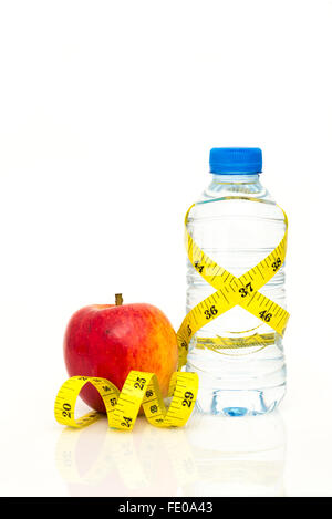 Water bottle wrapped in yellow imperial tape measure with red apple isolated on white background with copy space - Stock Photo