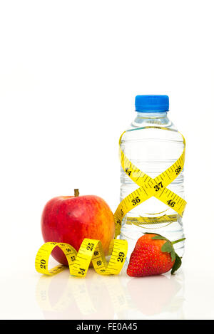 Water bottle wrapped in yellow imperial tape measure with red apple and strawberry isolated on white background - Stock Photo