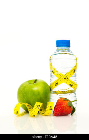 Water bottle wrapped in yellow imperial tape measure with green apple and strawberry  on white background with copy - Stock Photo