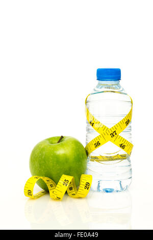 Water bottle wrapped in yellow imperial tape measure with green apple and isolated on white background with copy - Stock Photo