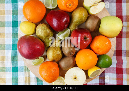 Pile of fresh fruit on colored kitchen towel - Stock Photo