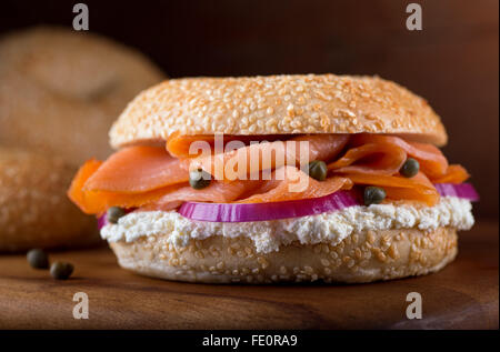 A delicious homemade sesame seed bagel with smoked salmon, whipped cream cheese, red onion, and capers. - Stock Photo