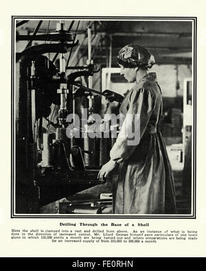 Woman working in a first world war munitions factory drilling through the base of a artillery shell - Stock Photo