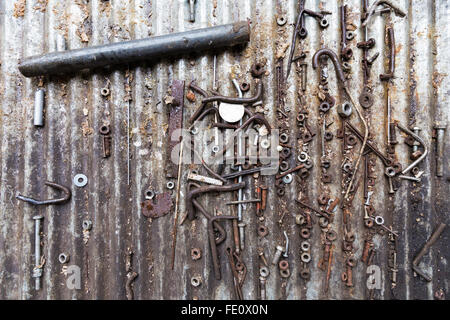 Detail of different rusty metallic bolts, screws, nuts and other parts on a metal surface background - Stock Photo