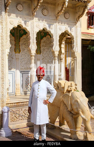 Indian guard standing at Rajendra Pol in Jaipur City Palace, Rajasthan, India. Palace was the seat of the Maharaja - Stock Photo
