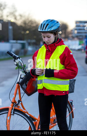 Cyclist put on safety clothing, bike helmet and reflecting vest for bike safety, good visibility at night in traffic - Stock Photo