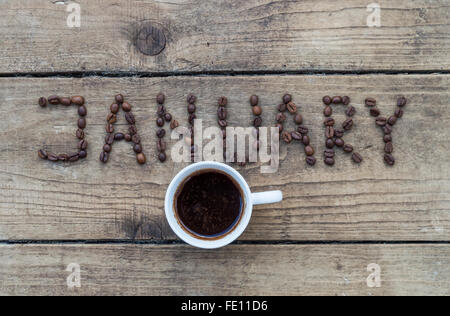 Cup of coffee on wooden background and January coffee beans - Stock Photo