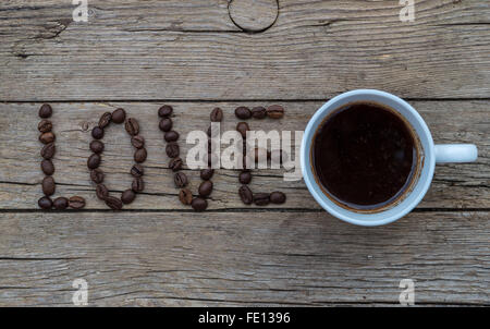 Cup of coffee on wooden background and LOVE coffee beans - Stock Photo