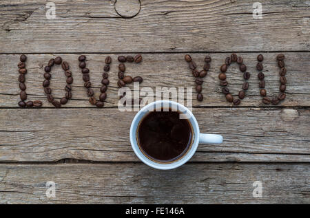 Cup of coffee on wooden background and LOVE YOU coffee beans - Stock Photo