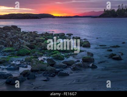 Vancouver Island, British Columbia: Setting sun over a rocky point at MacKenzie Beach near Tofino - Stock Photo
