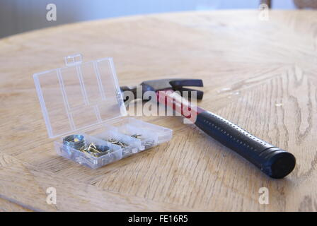 Hammer, nails and other tools used to hang pictures on the wall. - Stock Photo