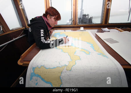 Venice, Italy. 03rd Feb, 2016. A member of crew of the Bob Barker ship with navigation chart in the control room - Stock Photo