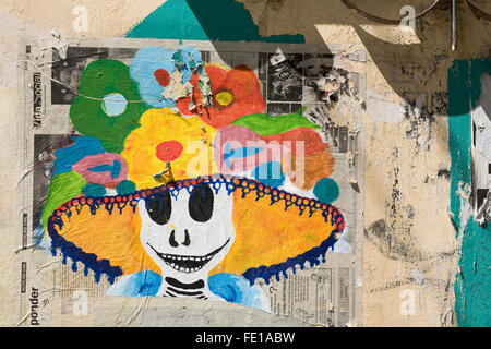 Humorous Day of the Dead graffiti art depicting a smiling skeleton in a flowered hat, Oaxaca City, Oaxaca, Mexico - Stock Photo