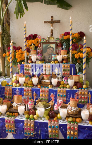 Traditional commemorative altar decorated with elaborate offerings of food, flowers and candles for Day of the Dead, - Stock Photo