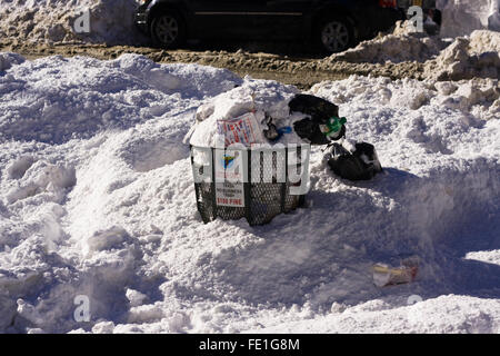 Overflowing Trash Can partially covered in 2 feet of snow on a street corner in New York City - Stock Photo
