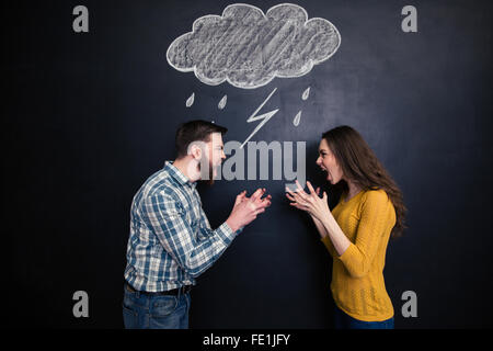 Quarrelling young couple standing against background of chalkboard and screaming on each other - Stock Photo
