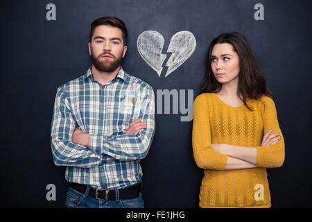 Portrait of young couple after argument standing separately with hands folded over blackboard background - Stock Photo