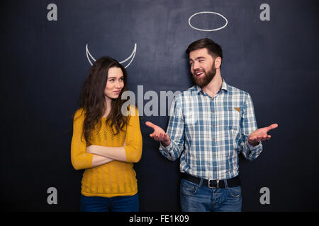 Smiling young man and woman imitating devil and angel standing over chalkboard background - Stock Photo