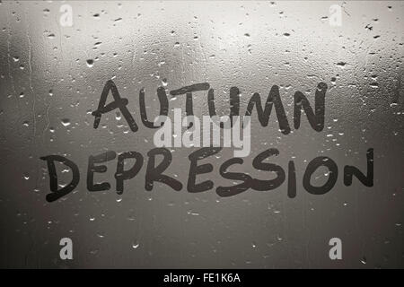 Inscription autumn depression on the fogged window on autumn rainy day - Stock Photo
