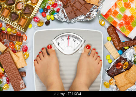 Unhealthy diet - overweight. Feet on bathroom scale and chocolate, jelly cubes, candies, chocolate bars, cookies, - Stock Photo