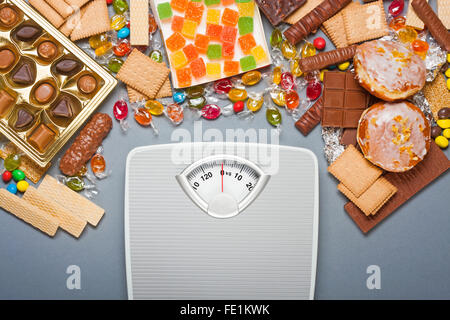 Unhealthy diet concept - overweight. Bathroom scale and chocolate, jelly cubes, candies, chocolate bars, cookies, - Stock Photo
