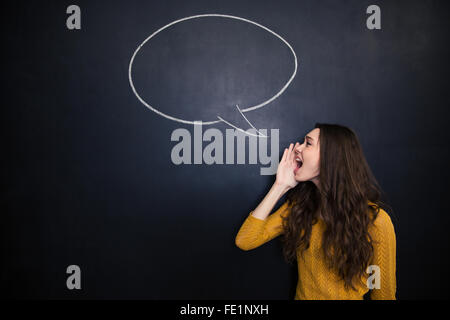 Profile of charming young woman standing and screaming against background of chalkboard with drawn blank speech - Stock Photo