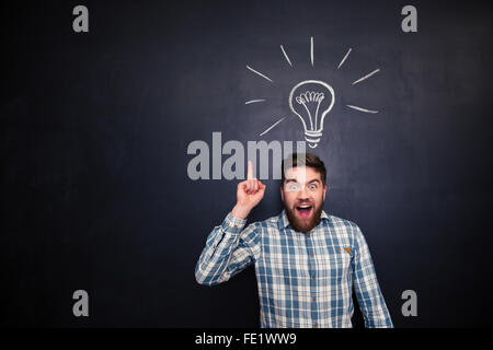 Excited bearded young man in checkered shirt pointing up over blackboard background with drawn light bulb - Stock Photo