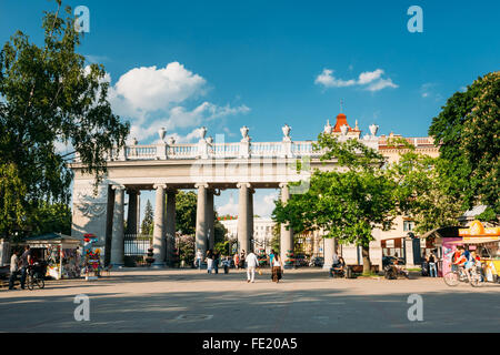 Main pillared entrance into Gorky Park in Minsk, Belarus. People walking to Gorky park at summer evening - Stock Photo