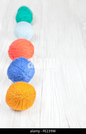 Yarn balls on wooden background, space for text. - Stock Photo