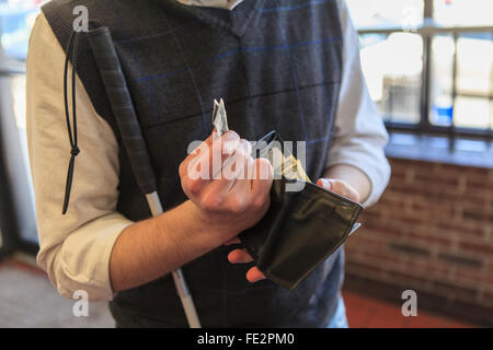 Young blind man with cane counting his money - Stock Photo