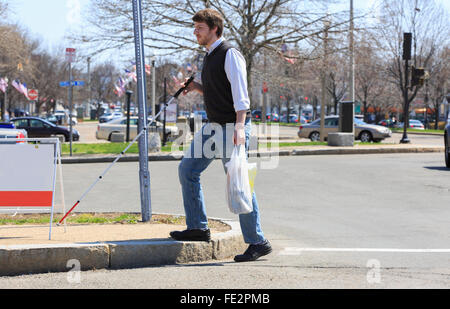 Young blind man walking in his neighborhood after shopping - Stock Photo