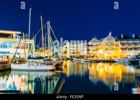 Night Scenery View of floating houses, vessel, yacht in Puerto Marina, Malaga. Deep blue sky and bay water with - Stock Photo