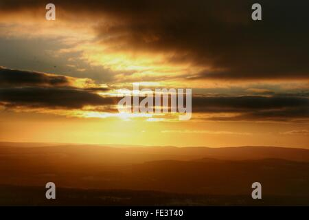 Scenic View Of Cloudy Sky Over Mountains During Sunset - Stock Photo
