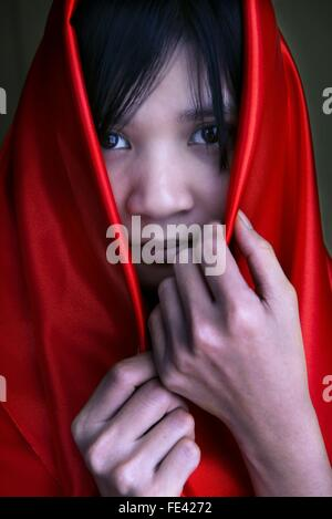 Portrait Of Young Woman Covered In Red Scarf - Stock Photo