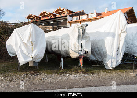 sailboats standing on the land wrapped for winter - Stock Photo
