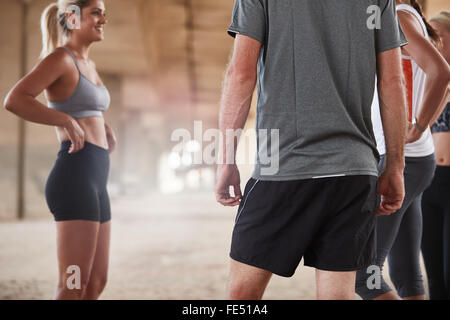 Cropped shot of young people taking break in running training. Athletes relaxing and talking after jogging. - Stock Photo