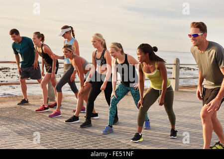 Marathon runners taking the position for the start of race. Young people about to start a running race on seaside - Stock Photo