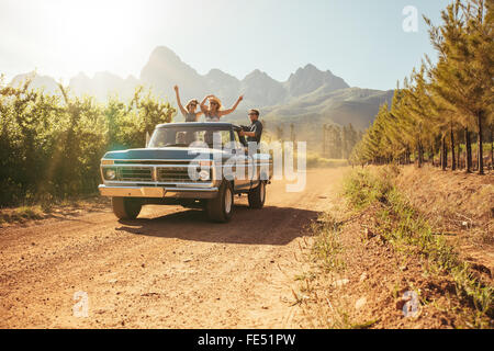 Friends having fun in the open back of a vintage truck on a summer day in countryside. Young men and woman enjoying - Stock Photo