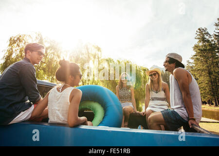 Group of young friends sitting in the back of a pickup truck with inflatable tubes going on a summer holidays on - Stock Photo